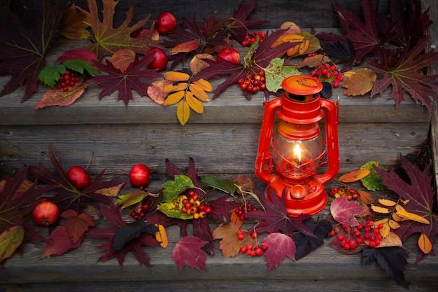 Осенний фон. горящий фонарь на ступенях крыльца, покрытых осенними листьями и ягодами.