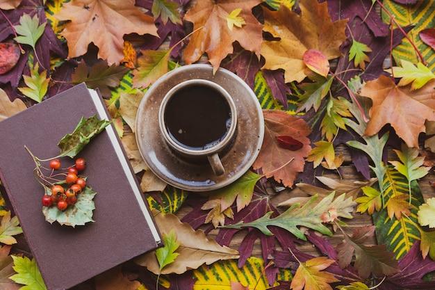 Осенний фон. осенние листья: чашка горячего кофе и книга на деревянном столе.