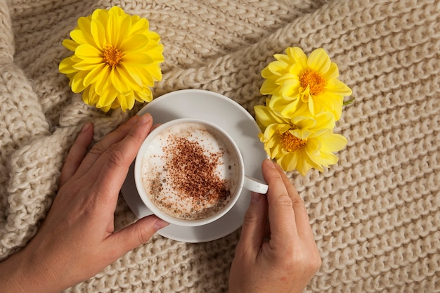 Autumn background, a cup of hot drink in female hands and a knitted plaid