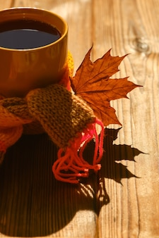 가을 배경 - 나무 탁자에 부드러운 햇빛 아래 따뜻한 스카프와 마른 가을 잎을 넣은 차 한 잔. 아늑한 집에서 가을 시간을 보내는 개념, 복사 공간