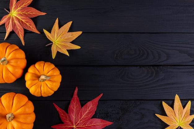 Осенний фон декор из кленовых листьев и тыкв на черном деревянном