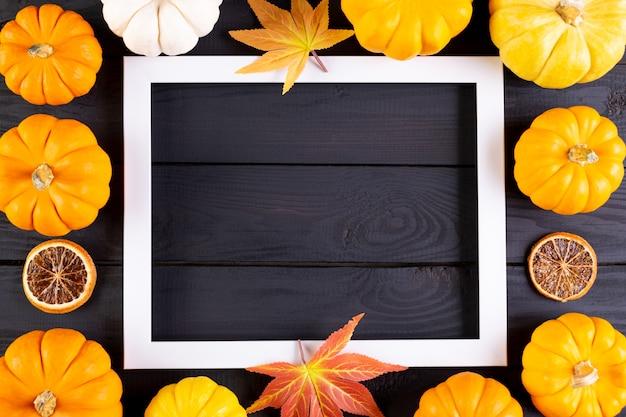 Осенний фон декор из кленовых листьев и тыкв с фоторамкой на черном деревянном