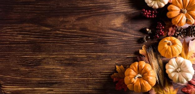 古い木製の背景に乾燥した葉とカボチャから秋の背景の装飾。フラットレイ、秋のコピースペースと感謝祭のコンセプトの上面図。