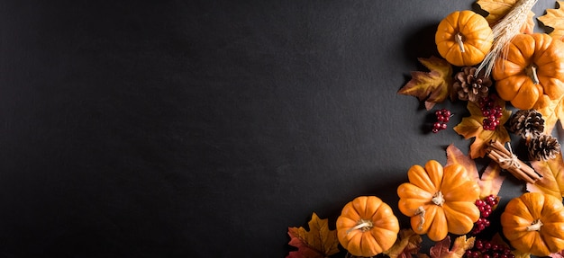 Autumn background decoration from dry leaves and pumpkin on dark wooden background. flat lay, top view for autumn, fall, thanksgiving concept.