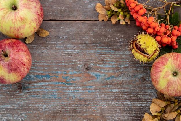 古い木製のテーブルにヴィンテージの場所を設定して落ち葉や果物から秋の背景。感謝祭のコンセプト。