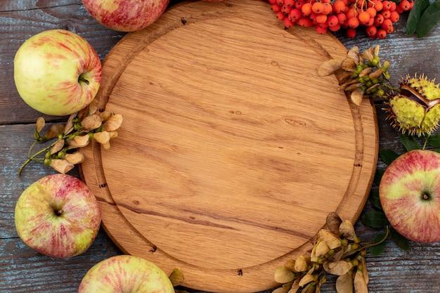 落ち葉や古い木製のテーブルにヴィンテージの場所の設定と果物から秋の背景。感謝祭の日のコンセプト