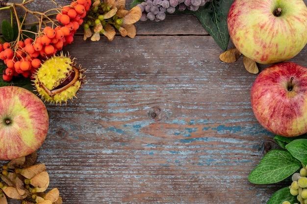 오래된 나무 테이블에 빈티지 장소가 있는 낙엽과 과일의 가을 배경. 추수 감사절 개념입니다.