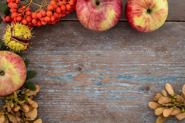 Autumn background from fallen leaves and fruits with vintage place setting on old wooden table. thanksgiving day concept.