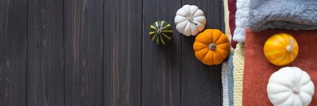 さまざまなウールニットのセーターやカボチャと暖かい色の秋の背景。バナー