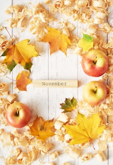 Autumn background of leaves, apples and flowers.