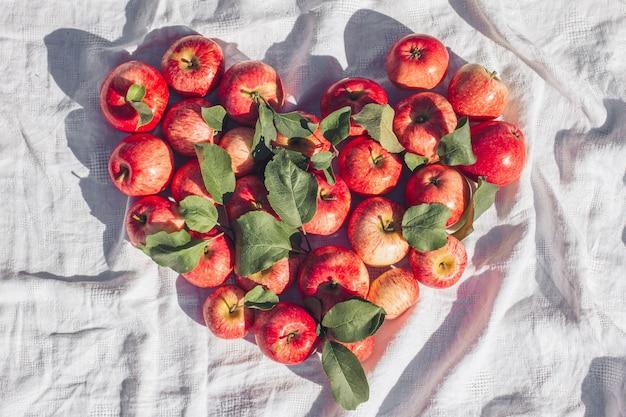 Осенний фон маленького красного яблока и листьев в форме сердца на бежевом фоне льняной ткани. пустое место для копирования вид сверху