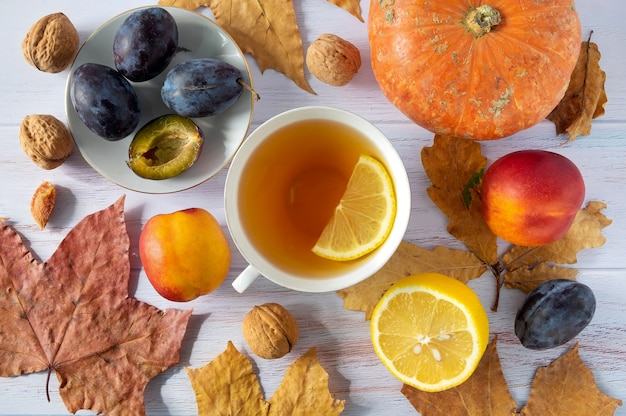 お茶、小さなカボチャ、レモン、プラム、ネクタリン、クルミとカップの葉の秋の背景