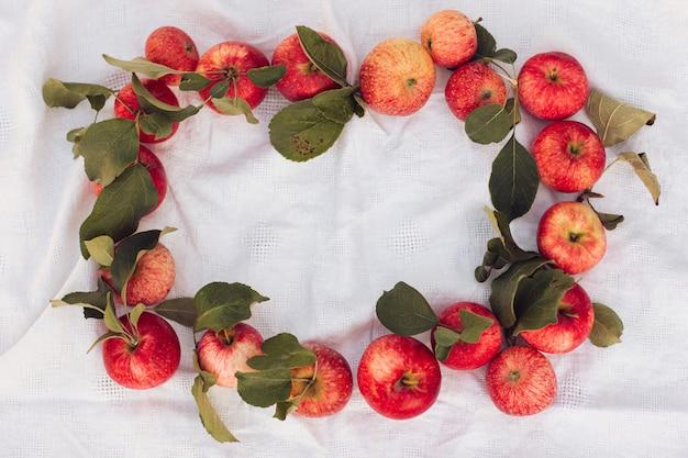 Осенний фон маленького красного яблока и листьев на фоне белья льняной ткани. пустое место для текста. вид сверху