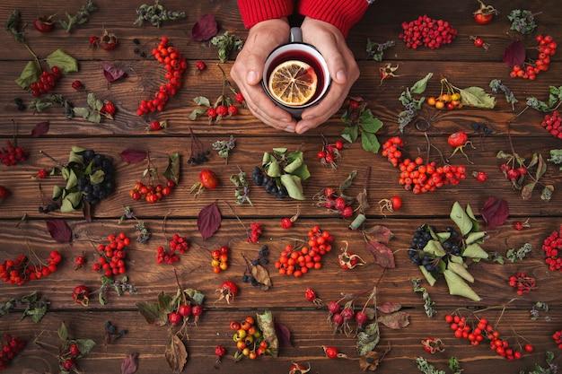 Осенний фон. чай с лимоном, ягодами и листьями на деревянном столе.