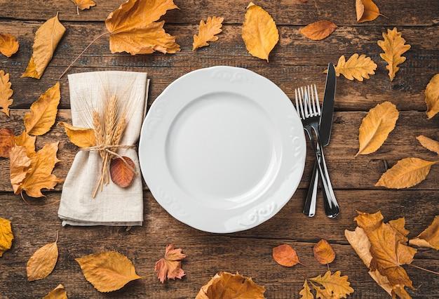 Осенний фон с тарелкой салфетки и столовыми приборами на деревянном фоне с листьями