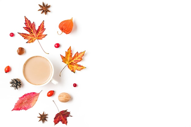Autumn background with coffee cup, autumn leaves, flowers, nuts and berries isolated