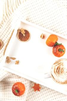 Осенний фон с копией пространства и тыквенный латте со взбитыми сливками и сиропом на белом подносе с ...