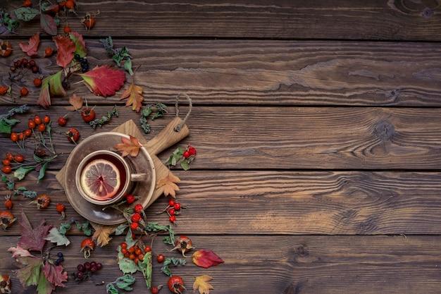 コピースペースと秋の背景。木製のテーブルにレモン、葉、ベリーとお茶。