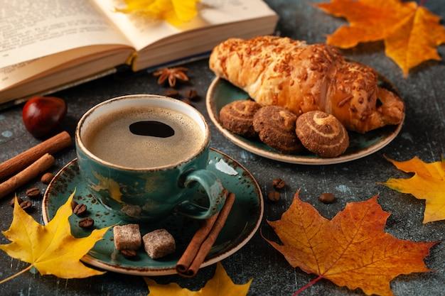ブラックコーヒー、クロワッサン、秋の装飾のカップと秋の背景