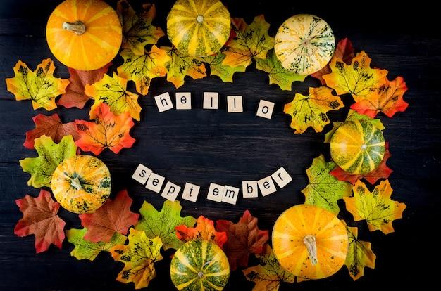 Осенний фон с декоративными тыквами, листьями и текстом привет сентябрь на деревянном столе
