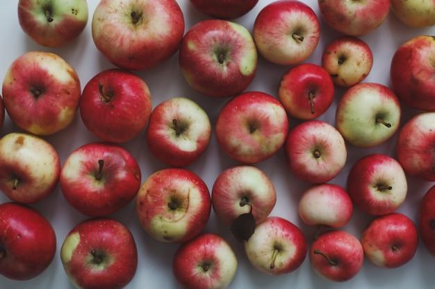 Осенний фон со свежими спелыми красными яблоками, изолированными на белом вид сверху