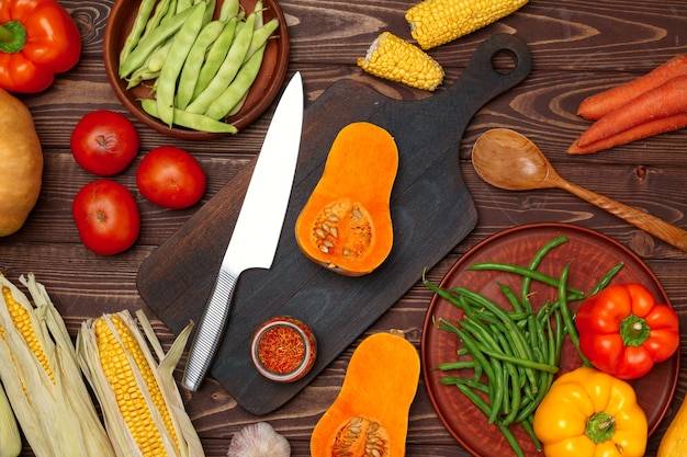 Autumn background with fresh vegetables and wooden cutting board