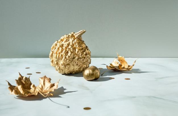 金のカボチャと葉、大理石のテーブルの秋の装飾、コピースペースと秋の背景