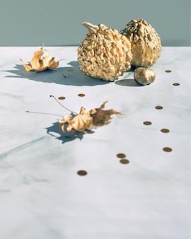 黄金のカボチャと乾燥した葉と秋の背景。秋の装飾、大理石のコピースペース