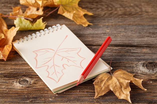 Autumn background with leaves of maple and acorns a on wooden background. paper with a pencil in the autumn background, place for text