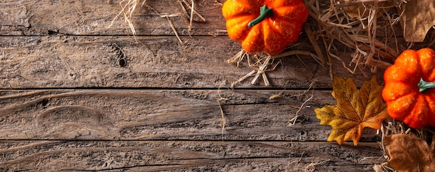 Autumn background with leaves and pumpkins on wooden background