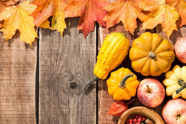 カエデの葉、カボチャ、リンゴと秋の背景