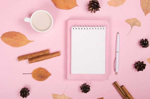Autumn background with notepad, cinnamon and leaves on pink background