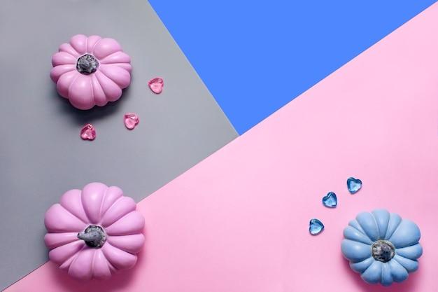 Осенний фон с розовыми и голубыми тыквами и стеклянными сердечками в пастельных тонах
