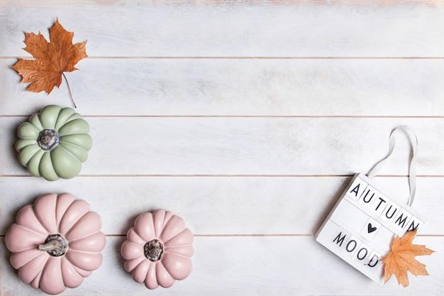 ピンクと緑のカボチャとパステル調の葉の秋の背景、碑文の秋の気分のライトボックス、コピースペース