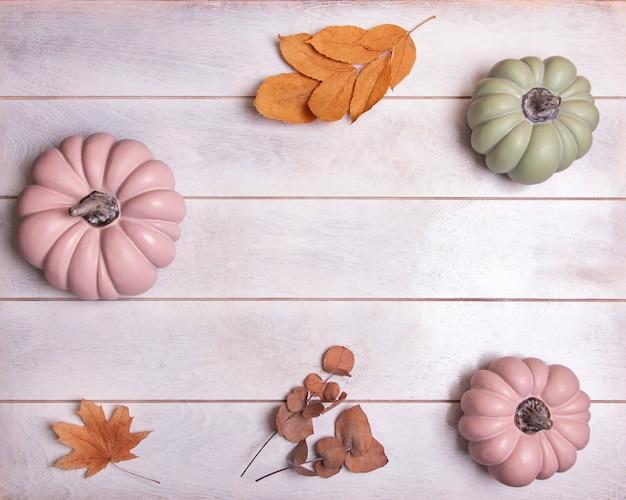 ピンクと緑のカボチャとパステル調の葉の秋の背景、コピースペースの上面図