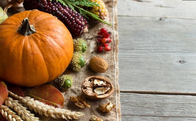 灰色の木製テーブルテーブルの上のカボチャと秋の背景をクローズアップ