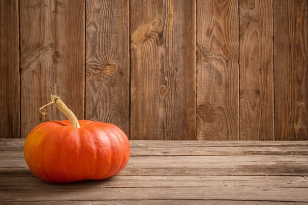 Autumn background with pumpkin on wooden board