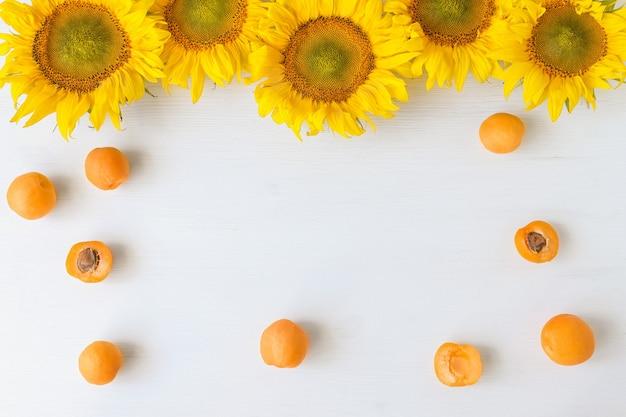 Осенний фон с подсолнухами и оранжевыми персиками, лежащими на деревянном столе с копией пространства