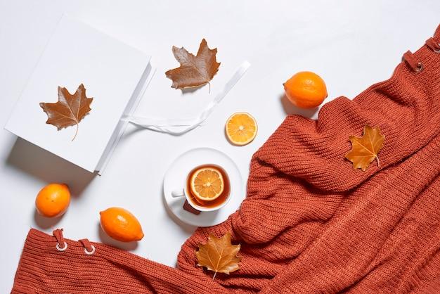 Осенний фон с чаем и вязанным свитером на белом фоне горячий травяной чай с лимоном и апельсином ...