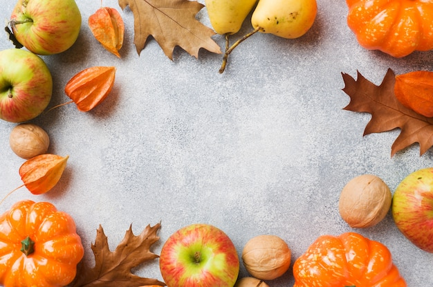Autumn background with yellow leaves, pumpkins apples pears and nuts