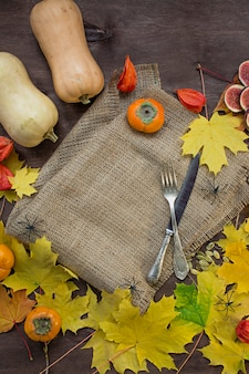Autumn background with yellow maple leaves, figs, persimmons and pumpkins.