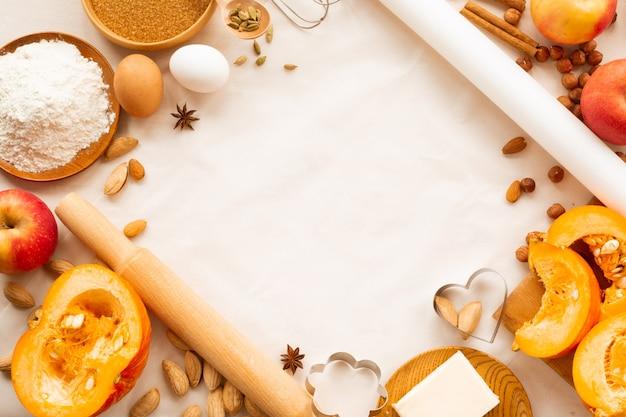 Осенняя выпечка фон границы кадра дизайн с копией пространства для текста. готовим ингредиенты тыква, яблоки, пшеница, мед, масло, мука, орехи, тонирование, ярко-оранжевые цвета