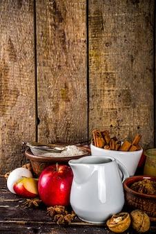秋のベーキングコンセプト。食材、スパイス、調理器具を使ったベーキングの背景を調理します。素朴な木製の背景のコピースペースで、伝統的な秋のアップルパイを焼くために必要なすべて
