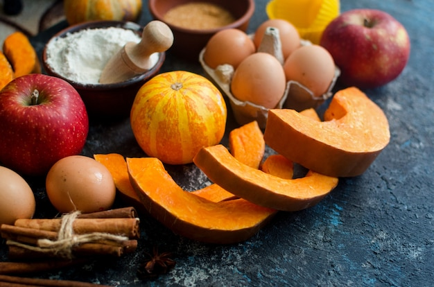 Autumn baking concept. frame with pumpkin, apple, nuts, cinamon, egg and flour on the wood table. cooking baking process with ingredients. top view. copy space,