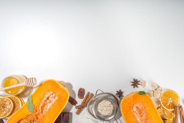 Концепция осенней выпечки, сырые ингредиенты для приготовления сладких осенних десертов, пироги - половинки тыквы, специи, сахар, овес, яйца, мука, белый фон с копией пространства