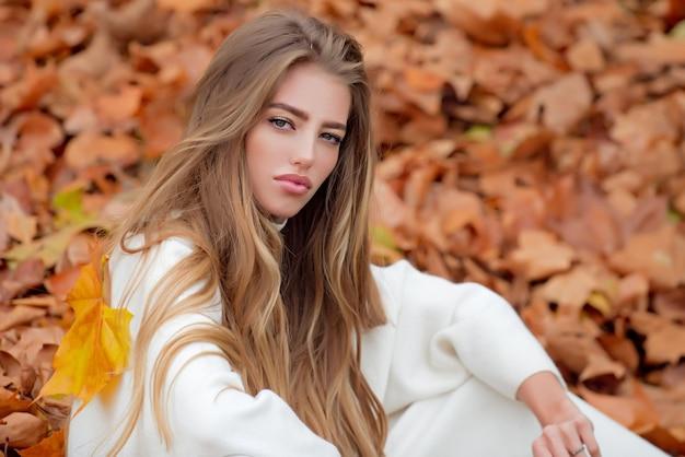Autumn, beautiful girl in maple, yellow leaves.