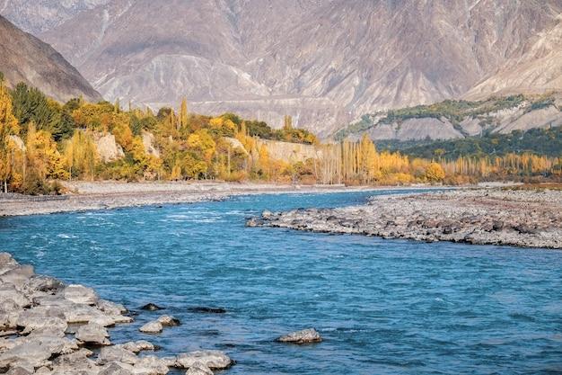 Autumn blue water of gilgit river flowing through gupis, ghizer, gilgit baltistan, pakistan