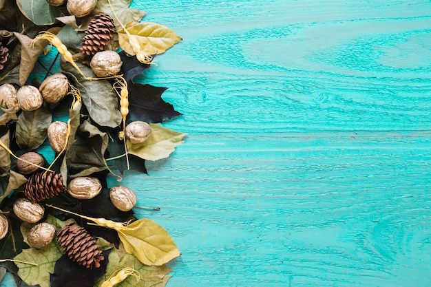 Autumn blue wooden background with leaves, pine cones and nuts