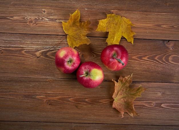 古い木製のテーブルの上のリンゴと落ち葉からの秋の境界線。