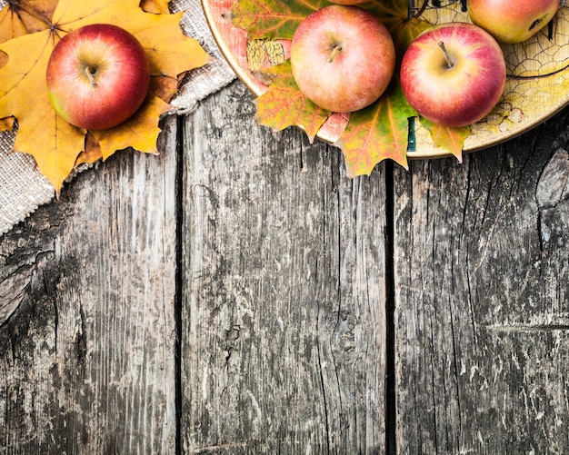 Autumn border from apples and fallen leaves on old wooden table. thanksgiving day concept